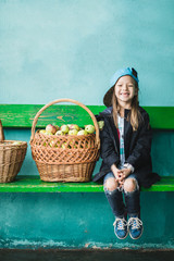 Cheeky little girl sitting on a green bench next to the big basket of apples