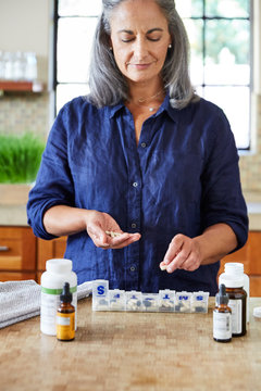 Mature woman organizing her health supplements in the kitchen