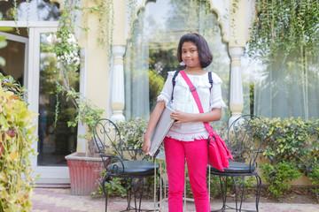 Teenage girl standing with laptop