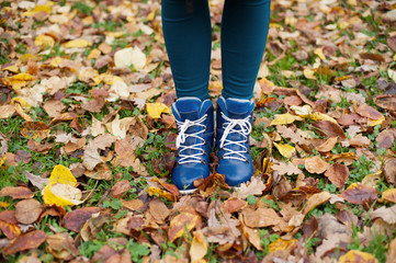 Bright blue boots among autumn fallen leaves