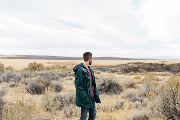 Lifestyle portrait of young adult man wearing fall coat in high desert dry grass field