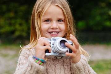 Portrait of a little girl holding an old camera.