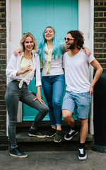 Three cool fashionable people in front of a bright blue door