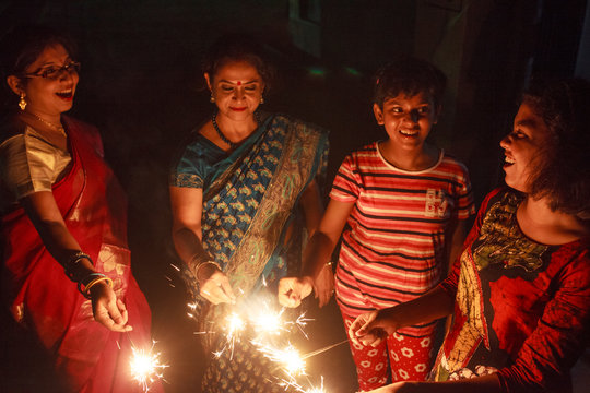 Teenage girls and Indian women lighting sparkle and celebrating