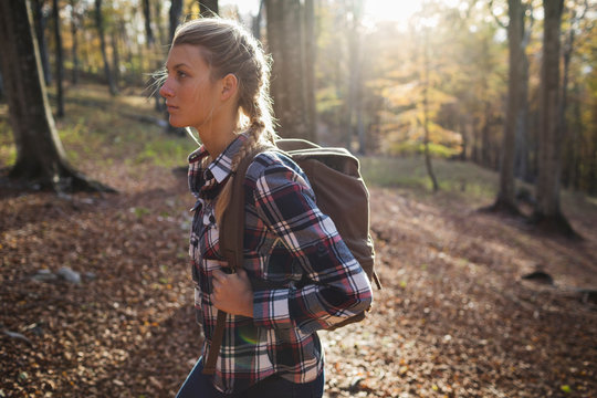 Young woman with backpack walking in the woods