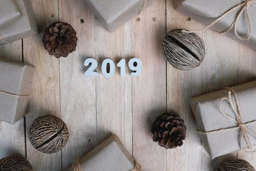 Happy new year 2019 background concept, gift and pine cone decoration on vintage wooden background, copy space