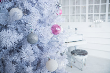 White Christmas tree decorated with silver and pink ornaments at the piano background.Winter scene. New Year decoration.Xmas interior design includes decorated Christmas tree.Selective focus.Classical