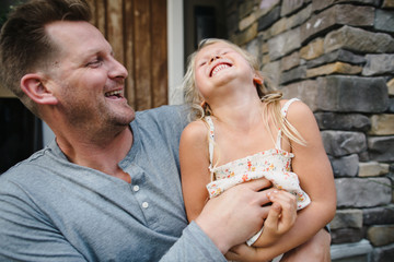 Dad tickling daughter and laughing outside house