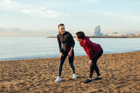 Young mother and her daughter practicing sport on the beach in autumn.