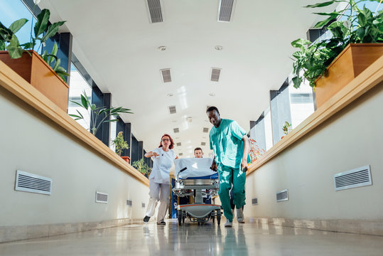 Medics running with bed in hospital