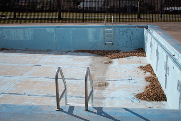 empty urban pool with grafitti and leaves