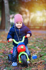 Cute little kid boy in warm autumn clothes having fun with tricycle.