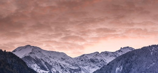 Wall Mural - panorama winter mountain landscape with forests in fall colors and snow-capped mountain peaks and valleys under an expressive sunset sky in the Swiss Alps above Bad Ragaz