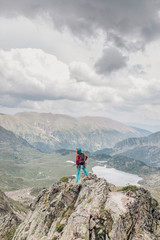 woman alpinist standing on the top of a high summit