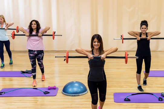 Senior women working out in gym with her instructor