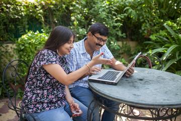 Indian couple enjoying and making fun with laptop