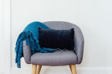 tub chair with cushion and throw rug, against plain wall