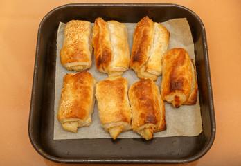 Seven freshly baked bourekas on pan in two rows