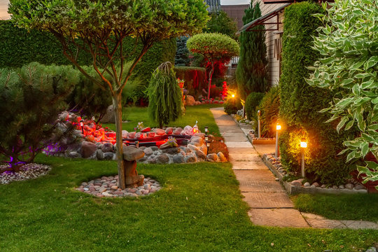 Garden illuminated by lamps in evening