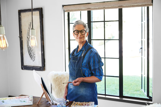 Artist portrait of mature woman with grey hair in her art studio in California