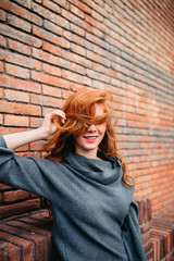 Young redhead woman playing with her hair