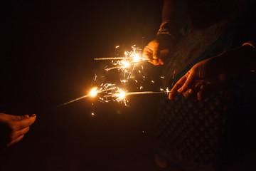 Woman's hand holding sparkler and celebrating festival
