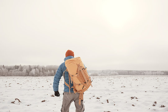 tourist view from the back / a man with a backpack goes through the winter forest, view of the outgoing