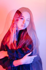 Double exposure of a woman with pink and purple lighting