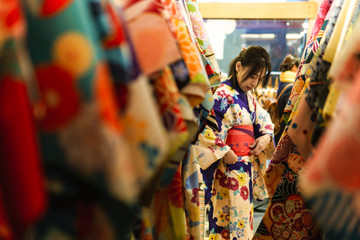 Young asian woman dress up with japanese kimono in kimono rental shop in japan Wall mural