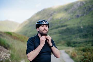 Man putting on his bicycle helmet