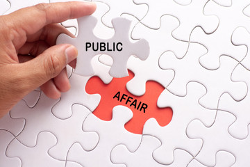 Hand holding piece of jigsaw puzzle with word PUBLIC AFFAIR