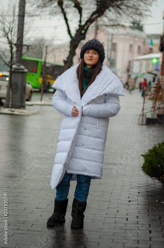 0edb344959 Fashion portrait of pretty smiling hipster woman in a white coat jacket