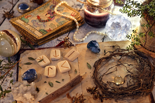 Open diary book with runes, dried herbs and tarot cards on table. Magic gothic ritual. Wicca, esoteric and occult background