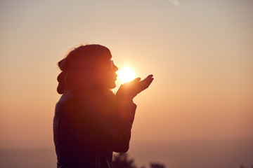 Woman with praying arms enjoying the sunrise / sunset time.