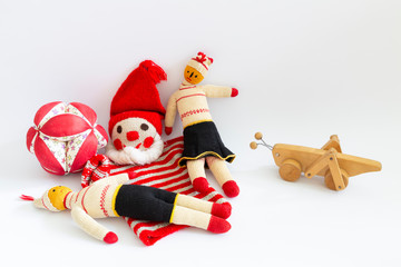 Front view of funny vintage children toys on white background. Assortment consists of a clown, a male doll, a female doll, a ball and a wooden grasshopper.