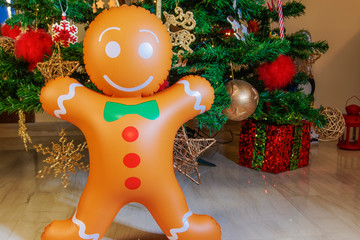 Large inflatable gingerbread man on a Christmas tree. Air blown seasonal figure before an illuminated artificial Christmas tree with lights and colorful decorations.