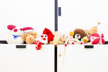 Front view of funny vintage children toys in a wardrobe drawer. Assortment consists of a clown, a squirrel, a bunny, dolls, a ball, a teddy bear, a wooden snail and a wooden grasshopper.