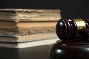 Judge gavel beside pile of books on wooden background