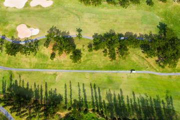 ゴルフ場の横を一台の車が走っている風景