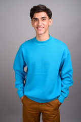 Young happy Persian teenage boy smiling against gray background