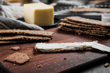 Useful rye crispbread on a wooden board against a dark background