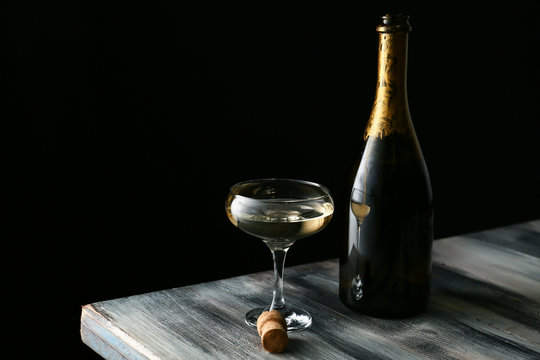 Glass and bottle of champagne on wooden table against dark background