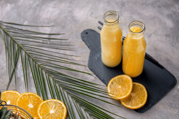 Bottles of tasty yellow smoothie with fruits and tropical leaf on grey table