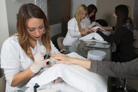 Three Manicurist At Work Applying Nail Polish, Filing Fingernails With Nail File, Polishing And Painting Fingernails At Beauty Salon