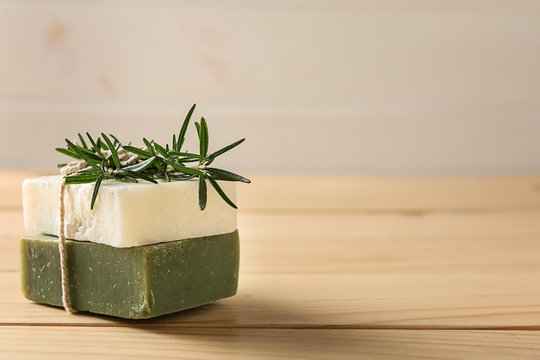 Soap bars with rosemary on wooden table