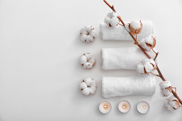 Flat lay composition with clean towels, burning candles and cotton flowers on white background