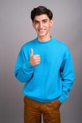 Young happy Persian teenage boy smiling and giving thumb up