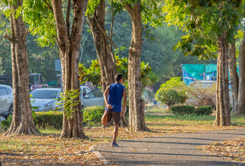 Asian man is warmed up before exercise in the park.