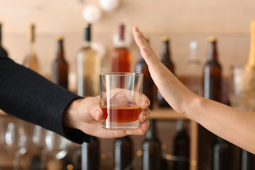 Man with glass of whiskey and woman refusing to drink in bar