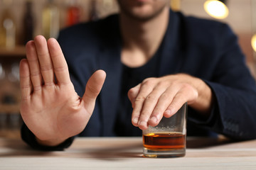 Man with glass of whiskey at table refusing to drink
